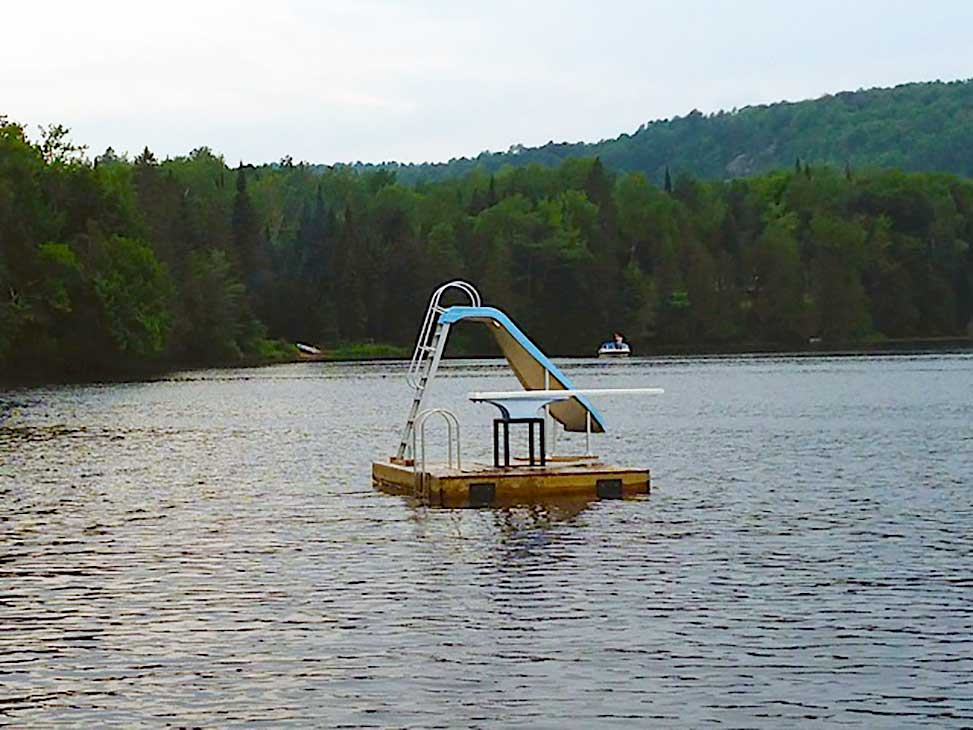 A floating raft with waterslide and diving board is shared by all cottages